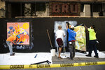 Workers affix posters to a boarded up business in Philadelphia, Monday, May 4, 2020. The Center City District and Mural Arts Philadelphia posted the original works on multiple locations in an effort to enhance the neighborhood awash with business shuttered to help curb the spread of coronavirus. (AP Photo/Matt Rourke)