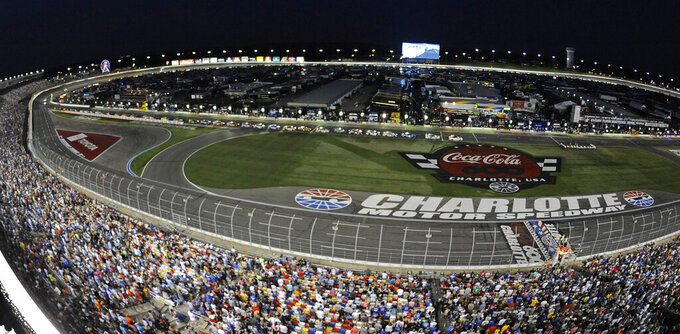 Cars are stopped on pit road as fans stand for a moment of remembrance at the halfway point during the NASCAR Cup Series auto race at Charlotte Motor Speedway in Concord, N.C., Sunday, May 26, 2019. (AP Photo/Mike McCarn)