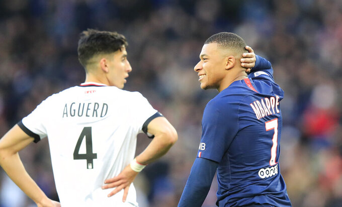PSG's Kylian Mbappe, right, reacts during the French League One soccer match between Paris-Saint-Germain and Dijon, at the Parc des Princes stadium in Paris, France, Saturday, Feb. 29, 2020. (AP Photo/Michel Euler)