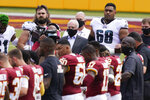Philadelphia Eagles team owner Jeffrey Lurie, center, joins members of the Philadelphia Eagles and Washington Football Team on the field before the start of an NFL football game, Sunday, Sept. 13, 2020, in Landover, Md. (AP Photo/Alex Brandon)