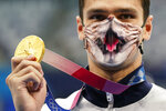 Evgeny Rylov, of Russian Olympic Committee, pauses for photos after winning the gold medal in the men's 200-meter backstroke final at the 2020 Summer Olympics, Friday, July 30, 2021, in Tokyo, Japan. (AP Photo/Jae C. Hong)
