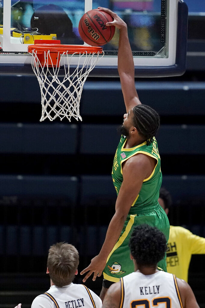Oregon guard LJ Figueroa, top, dunks against California during the second half of an NCAA college basketball game in Berkeley, Calif., Saturday, Feb. 27, 2021. (AP Photo/Jeff Chiu)