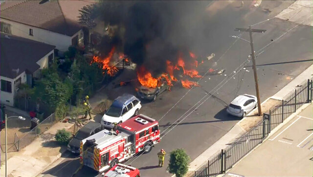 In this photo taken from video provided by KTLA-TV, is a small plane that crashed and burned on a street just outside a small airfield in Los Angeles' San Fernando Valley, Thursday, Nov. 12, 2020. A KTLA news helicopter overhead showed fire burning parked cars in the street and on a lawn of a house in a neighborhood off one end of Whiteman Airport's single runway in the Pacoima area about 15 miles northwest of downtown Los Angeles. (KTLA-TV via AP)