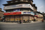 Kashmiris walk in a closed market area during a strike called by separatists in Srinagar, Indian controlled Kashmir, Saturday, Oct. 31, 2020. Kashmir's main separatist grouping called the strike to protest new land laws that India enacted on Tuesday, allowing any of its nationals to buy land in the region. Pro-India politicians in Kashmir have also criticized the laws and accused India of putting Kashmir's land up for sale. The move exacerbates concerns of Kashmiris and rights groups who see such measures as a settler-colonial project to change the Muslim-majority region's demography. (AP Photo/Mukhtar Khan)