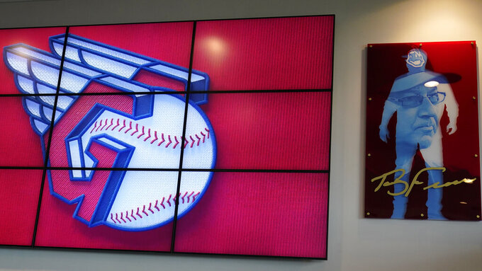 The new Cleveland Indians logo is displayed on a screen next to art work, Friday, July 23, 2021, in Cleveland. Known as the Indians since 1915, Cleveland's Major League Baseball team will be called Guardians. The ballclub announced the name change Friday, effective at the end of the 2021 season. (AP Photo/Tony Dejak)