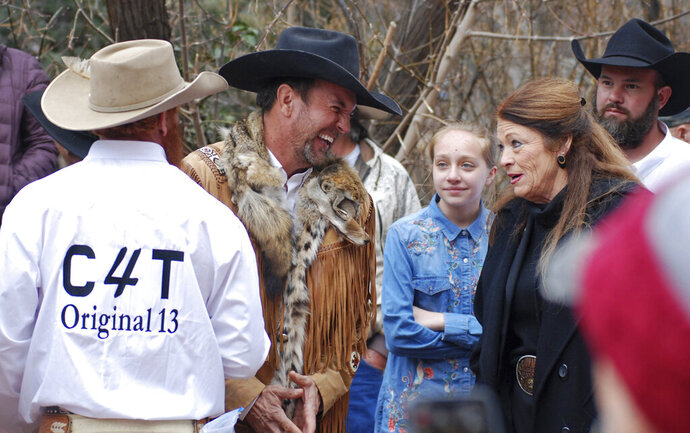 FILE - In this March 12, 2019, file photo, Cowboys for Trump leader and Otero County Commissioner Couy Griffin, center, talks with Republican New Mexico state Rep. Candy Ezzell of Roswell, N.M., at a protest against gun control and pro-abortion rights legislation outside the New Mexico State Capitol, in Santa Fe, N.M. A New Mexico county official who runs a group called
