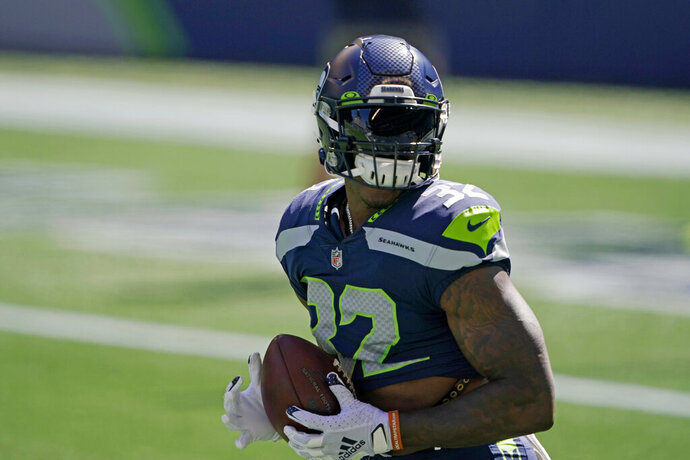 Seattle Seahawks running back Chris Carson holds the football as players warm up for an NFL football scrimmage Wednesday, Aug. 26, 2020, in Seattle. (AP Photo/Ted S. Warren)