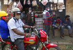 People wearing face masks as a precaution against the coronavirus shop at a market area in Bengaluru, India, Thursday, Oct. 29, 2020. India's confirmed coronavirus caseload surpassed 8 million on Thursday with daily infections dipping to the lowest level this week, as concerns grew over a major Hindu festival season and winter setting in. (AP Photo/Aijaz Rahi)