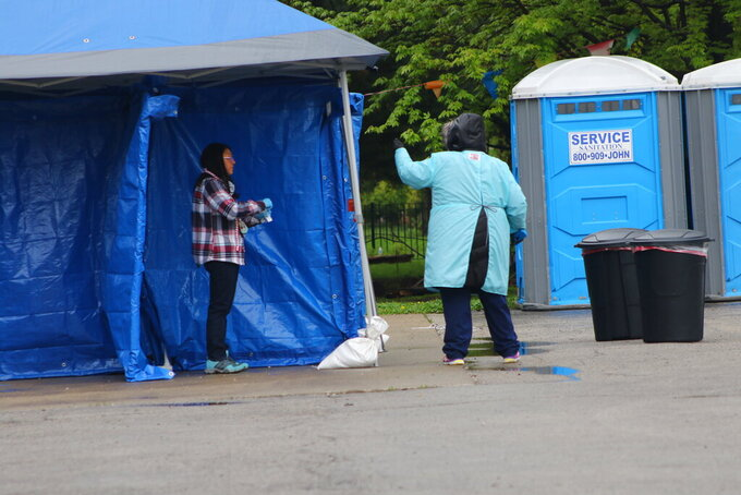 In this May 14, 2020 photo, a woman gets tested at a new testing site in the Little Village neighborhood of Chicago. Chicago's Little Village neighborhood is known as the heart of Mexican culture in the city. It's also located in the zip code area with one of the highest rates of positive coronavirus cases in the city. Across the country, states reporting racial data indicate similar trends, with overwhelmingly high rates of infection within the Latino population.  (AP Photo/Noreen Nasir)