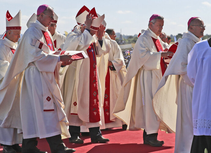 Bishop Juan Barros, second from right, arrives to attend a Mass celebrated by Pope Francis at the Maquehue Air Base in Temuco, Chile, Wednesday, Jan. 17, 2018. Many Chileans are furious over Francis' 2015 decision to appoint Barros, a bishop close to the Rev. Fernando Karadima, who the Vatican found guilty in 2011 of abusing dozens of minors over decades. Barros has always denied he knew what Karadima was doing when he was the priest's protege, a position that many Chileans have a hard time believing. (AP Photo/Alessandra Tarantino)