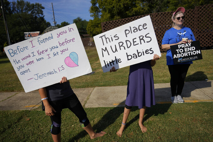 Anti-abortion protesters, including two adolescent girls, hold signs as they stand outside Hope Medical Group for Women, Saturday, Oct. 9, 2021, in Shreveport, La. As most of the women entered the clinic's parking lot, they were met by two groups of anti-abortion protesters, mostly men from East Texas who regularly make the trip to Shreveport. (AP Photo/Rebecca Blackwell)