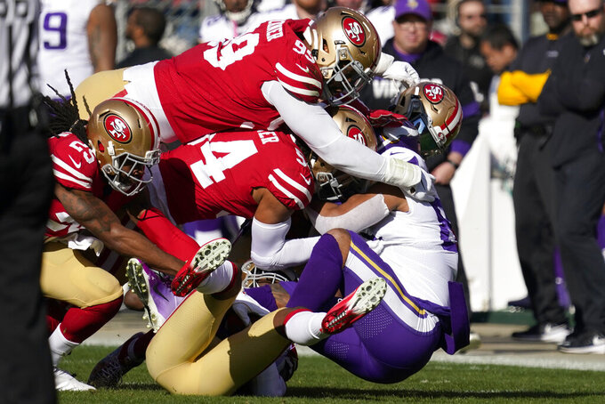 Minnesota Vikings tight end Irv Smith, right, is tackled by San Francisco 49ers cornerback Richard Sherman, left, defensive tackle DeForest Buckner, top, middle linebacker Fred Warner, center, and free safety Jimmie Ward, bottom, during the first half of an NFL divisional playoff football game, Saturday, Jan. 11, 2020, in Santa Clara, Calif. (AP Photo/Tony Avelar)