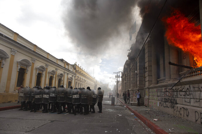 Flames shoot out from the Congress building after protesters set a part of the building on fire, in Guatemala City, Saturday, Nov. 21, 2020. Hundreds of protesters were protesting in various parts of the country Saturday against Guatemalan President Alejandro Giammattei and members of Congress for the approval of the 2021 budget that reduced funds for education, health and the fight for human rights. (AP Photo/Oliver De Ros)