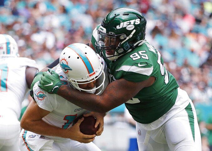 FILE - In this Nov. 3, 2019, file photo, New York Jets defensive tackle Quinnen Williams (95) sacks Miami Dolphins quarterback Ryan Fitzpatrick during the first half of an NFL football game in Miami Gardens, Fla. Williams was arrested for criminal possession of a weapon Thursday night, March 5, 2020, when he attempted to board a plane, police said in a statement. New York/New Jersey Port Authority Police said Williams, the team's first-round draft pick last season, was arrested at LaGuardia Airport around 9:15 p.m. and charged. Police said Williams has a permit in his home state of Alabama for the Glock 19 pistol he was carrying onto the flight. It was not immediately known whether the gun was loaded. (AP Photo/Wilfredo Lee, File)