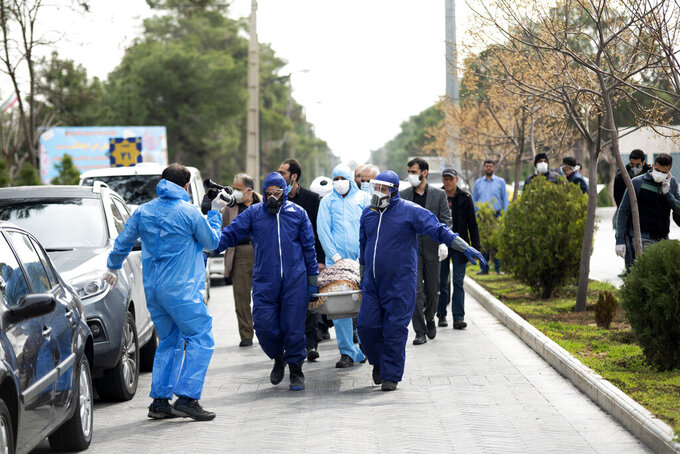 Men wearing protective gear carry the body of Fatemeh Rahbar, a lawmaker-elect from a Tehran constituency, who died on Saturday after being infected with the new coronavirus, at Behesht-e-Zahra cemetery, just outside Tehran, Iran, Sunday, March 8, 2020. Rahbar previously served three terms as lawmaker. With the approaching Persian New Year, known as Nowruz, officials kept up pressure on people not to travel and to stay home. Health Ministry spokesman Kianoush Jahanpour, who gave Iran's new casualty figures Sunday, reiterated that people should not even attend funerals. (Mehdi Khanlari/Fars News Agency via AP)