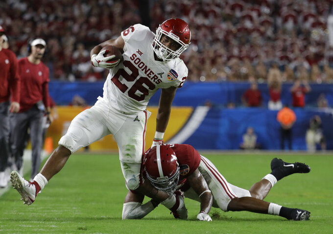 Alabama defensive back Saivion Smith (4) holds onto the foot of Oklahoma running back Kennedy Brooks (26), during the second half of the Orange Bowl NCAA college football game, Saturday, Dec. 29, 2018, in Miami Gardens, Fla. (AP Photo/Lynne Sladky)