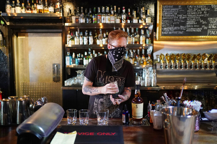 FILE - In this July 10, 2020, file photo, Davey Francis mixes drinks at Velveteen Rabbit, a cocktail bar in the Las Vegas Arts District, on the last night before they will have to close in Las Vegas. Bars in and around Las Vegas can reopen after this weekend with limited capacity, distance between customers and facial coverings all around, officials announced Thursday, Sept. 17, 2020. (AP Photo/John Locher, File)