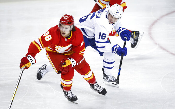 Toronto Maple Leafs' Mitchell Marner, right, chases Calgary Flames' Andrew Mangiapane during the third period of an NHL hockey game, Tuesday, Jan. 26, 2021 in Calgary, Alberta. (Jeff McIntosh/The Canadian Press via AP)