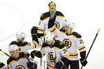 Boston Bruins center Curtis Lazar (20) celebrates with Bruins center Patrice Bergeron (37) after an NHL hockey game against the New Jersey Devils, Monday, May 3, 2021, in Newark, N.J. (AP Photo/Kathy Willens)