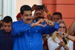Venezuela's President Nicolas Maduro, accompanied by first lady Cilia Flores, flashes a heart-hand symbol at supporters during an event at the Miraflores Presidential Palace to mark Youth Day, in Caracas, Venezuela, Wednesday, Feb. 12, 2020. (AP Photo/Matias Delacroix)