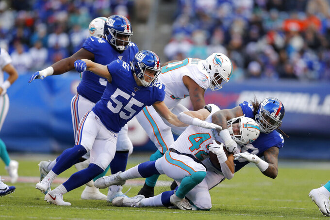 Miami Dolphins running back Patrick Laird (42) is tackled by New York Giants defensive end Leonard Williams (99) during the first half of an NFL football game, Sunday, Dec. 15, 2019, in East Rutherford, N.J. (AP Photo/Adam Hunger)