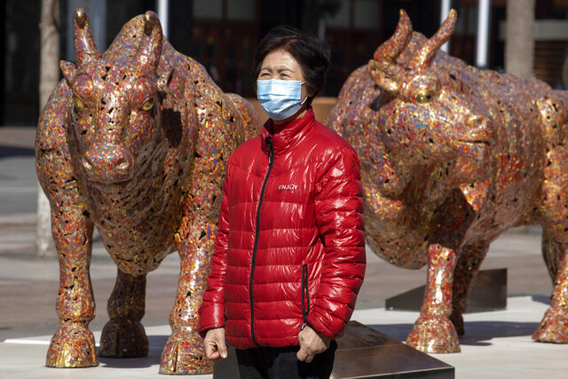 A woman wearing a mask stands near bull sculptures depicting prosperity along a retail street in Beijing on Tuesday, March 3, 2020. Asian shares rose Tuesday amid hopes that central banks will take action to shield the global economy from the effects of the coronavirus outbreak. (AP Photo/Ng Han Guan)