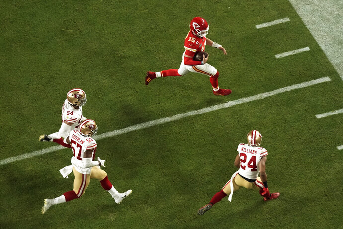 Kansas City Chiefs quarterback Patrick Mahomes (15) is pursued by San Francisco 49ers' K'Waun Williams (24), Dre Greenlaw (57), and Fred Warn (54), during the second half of the NFL Super Bowl 54 football game Sunday, Feb. 2, 2020, in Miami Gardens, Fla. (AP Photo/Morry Gash)