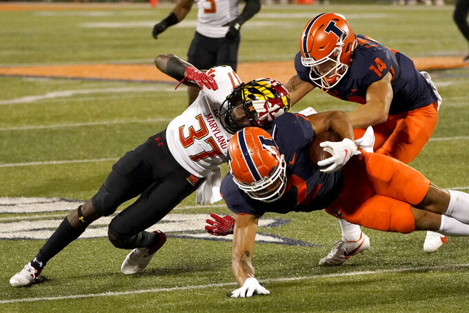 Maryland defensive back Lavonte Gater (37) tackles Illinois running back Chase Brown as wide receiver Casey Washington tries to make a block during the first half of an NCAA college football game Friday, Sept. 17, 2021, in Champaign, Ill. (AP Photo/Charles Rex Arbogast)