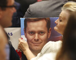In this photo taken Tuesday Oct. 8, 2019 a supporter of Poland's ruling right-wing party is holding a photo of one of the Law and Justice party's candidates at a convention in Warsaw, Poland ahead of Sunday parliamentary election in which the Law and Justice party is hoping to win a second term in power. (AP Photo/Czarek Sokolowski)
