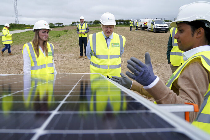 FILE - In this Wednesday, June 9, 2021 file photo, Prime Minister Boris Johnson, center, looks at a solar panel as he visits the Scottish Power Carland Cross Windfarm in Newquay, Cornwall, England. A report released on Wednesday, Sept. 15, 2021 by Climate Action Tracker says only one nation, tiny The Gambia in Africa, has plans in line with limiting warming to the agreed upon goal set by the 2015 Paris agreement. The United Kingdom is the only developed nation that comes even close. (AP Photo/Jon Super, Pool)