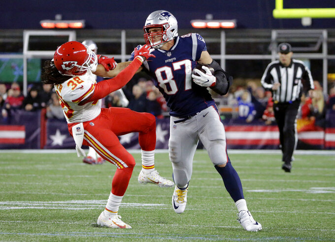 FILE - In this Oct. 14, 2018, file photo, New England Patriots tight end Rob Gronkowski (87) gives a stiff arm to Kansas City Chiefs free safety Ron Parker (38) after catching a pass during the second half of an NFL football game, in Foxborough, Mass. New England's mettle has been tested weekly. But after nabbing yet another a first-round bye, it's put the Patriots in position to make another deep playoff run. (AP Photo/Steven Senne, File)