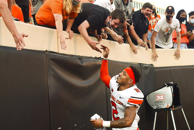 Oklahoma State wide receiver Tylan Wallace (2) celebrates with the student section following Oklahoma State's 27-13 win over West Virginia in an NCAA college football game Saturday, Sept. 26, 2020, in Stillwater, Okla. (AP Photo/Brody Schmidt)