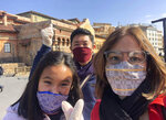 In this late February 2020, photo, Carlo Navarro poses behind his wife Evie and daughter Gia for a family photo while wearing face masks and gloves during a trip to Tokyo. When they visited Japan from the Philippines in February, they knew they were taking a chance with the coronavirus, but thought they would be spared if they took precautions. They wore masks and gloves and always had alcohol handy to sanitize their hands. Days after he was cleared and discharged from hospital, Navarro shared his COVID-19 experience on a Facebook public post. (Carlo Navarro via AP)