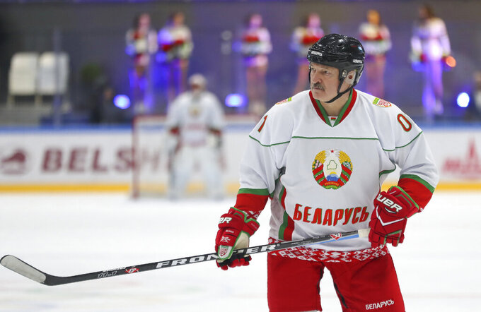 FILE In this file pool photo taken on Saturday, April 4, 2020, Belarusian President Alexander Lukashenko takes part in a hockey match during Republican amateur competitions in Minsk, Belarus.  Belarus' authoritarian President Alexander  Lukashenko faces a perfect storm as he seeks a sixth term in the election held Sunday, Aug. 9, 2020 after 26 years in office. Mounting public discontent over the worsening economy and his government's bungled handling of the coronavirus pandemic has fueled the largest opposition rallies since the Soviet collapse. (Andrei Pokumeiko/BelTA Pool Photo via AP, File)