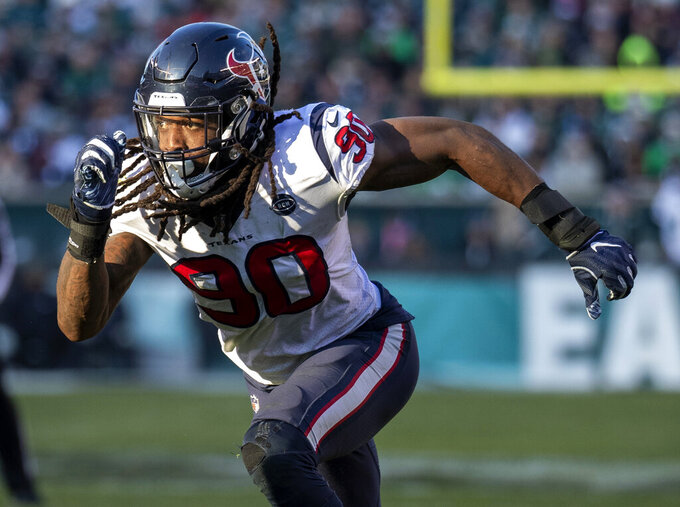 FILE- In this Dec. 23, 2018, file photo, Houston Texans outside linebacker Jadeveon Clowney (90) rushes during the NFL football game against the Philadelphia Eagles in Philadelphia. Fans worry that the summer rite in the NFL, training camp holdouts, won't affect their team's chances for a championship. This year's crop of no-shows includes an All-Pro receiver, the Saints' Michael Thomas; a standout offensive tackle who might be the key to the Redskins' offense, Trent Williams; and budding stars DEs Jadeveon Clowney of the Texans, Yannick Ngakoue of the Jaguars, and RB Melvin Gordon of the Chargers.  (AP Photo/Chris Szagola, File)