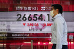 A man walks past a bank electronic board showing the Hong Kong share index at Hong Kong Stock Exchange Wednesday, Feb. 26, 2020. Asian shares slid Wednesday following another sharp fall on Wall Street as fears spread that the growing virus outbreak will put the brakes on the global economy. (AP Photo/Vincent Yu)