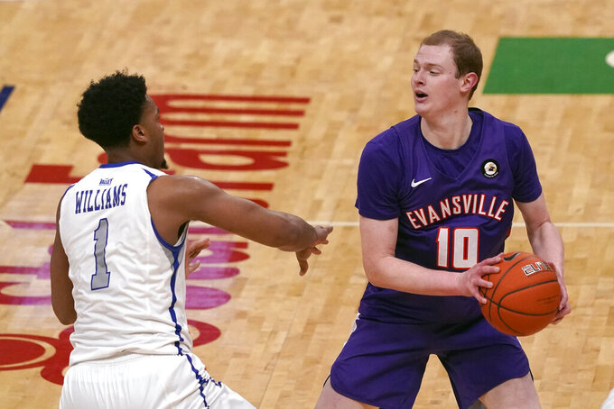 Evansville's Evan Kuhlman (10) looks to pass as Indiana State's Tre Williams (1) defends during the first half of an NCAA college basketball game in the quarterfinal round of the Missouri Valley Conference men's tournament Friday, March 5, 2021, in St. Louis. (AP Photo/Jeff Roberson)