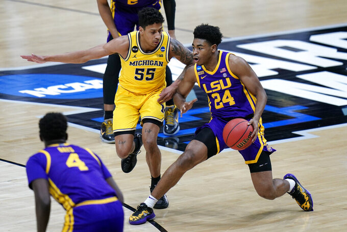 LSU guard Cameron Thomas (24) drives past Michigan guard Eli Brooks (55) during the first half of a second-round game in the NCAA men's college basketball tournament at Lucas Oil Stadium Monday, March 22, 2021, in Indianapolis. (AP Photo/AJ Mast)