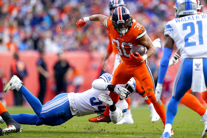 Denver Broncos running back Phillip Lindsay (30) is tripped up by Detroit Lions linebacker Steve Longa during the first half of an NFL football game, Sunday, Dec. 22, 2019, in Denver. (AP Photo/Jack Dempsey)