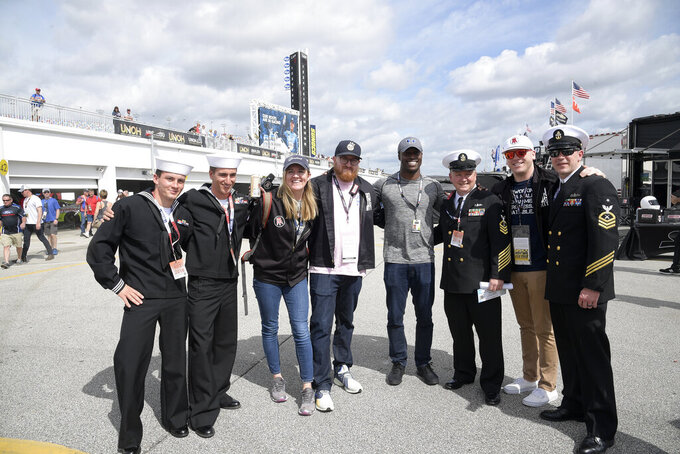 Driver Jesse Iwuji, center right, poses with military personal and representatives of Barstool Sports, while leading a tour of the garage area, during a practice session for the NASCAR Daytona 500 auto race at Daytona International Speedway Saturday, Feb. 16, 2019, in Daytona Beach, Fla. (AP Photo/Phelan M. Ebenhack)