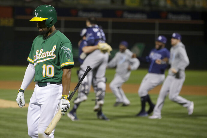 Oakland Athletics' Marcus Semien (10) walks off the field as Tampa Bay Rays players celebrate after defeating the Athletics in an American League wild-card baseball game in Oakland, Calif., Wednesday, Oct. 2, 2019. (AP Photo/Jeff Chiu)