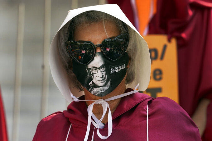 A demonstrator wears a mask with an image of Supreme Court judge Ruth Bader Ginsburg on it during a Women's March Saturday, Oct. 17, 2020, in Los Angeles. Thousands of women rallied in U.S. cities, to oppose President Donald Trump and his fellow Republican candidates in the Nov. 3 elections. (AP Photo/Marcio Jose Sanchez)