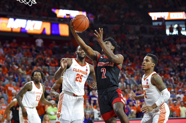 Louisville's Darius Perry (2) drives to the basket while defended by Clemson's Aamir Simms, left, and Al-Amir Dawes during the first half of an NCAA college basketball game Saturday, Feb. 15, 2020, in Clemson, S.C. (AP Photo/Richard Shiro)