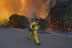 A firefighter runs to his firetruck while protecting a home along Crystal Springs Road while battling the Glass Fire in St. Helena, Calif., on Sunday, Sept. 27, 2020. (Jose Carlos Fajardo/Bay Area News Group via AP)