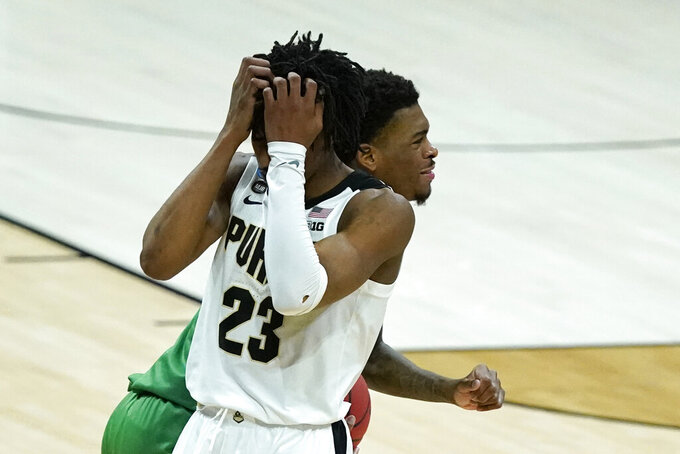 Purdue's Jaden Ivey (23) covers his face as North Texas's Javion Hamlet runs past during overtime of a first-round game in the NCAA men's college basketball tournament at Lucas Oil Stadium, Friday, March 19, 2021, in Indianapolis. North Texas defeated Purdue 78-69 in overtime. (AP Photo/Darron Cummings)