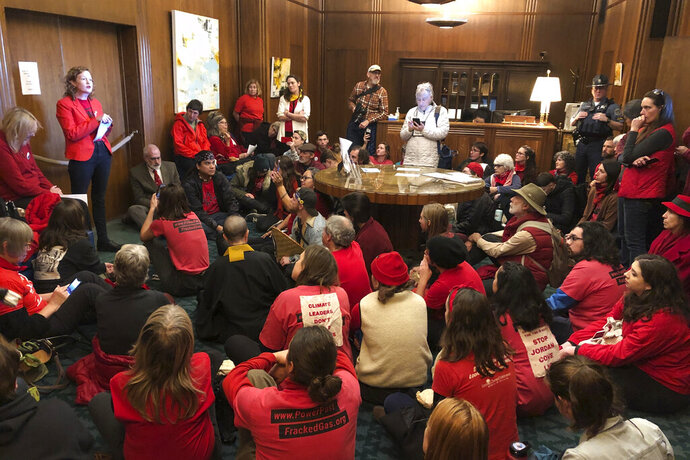 FILE - In this Nov. 21, 2019, file photo, demonstrators against a proposed liquid-natural gas pipeline and export terminal in Oregon sit in in the governor's office in the State Capitol in Salem, Ore., to demand Democratic Gov. Kate Brown stand against the proposal. The Jordan Cove pipeline is undergoing a permitting process and would end at a proposed marine export terminal in Coos Bay, Ore. Members of a federal regulatory agency on Thursday, Feb. 20, 2020, delayed a vote on the project, with one member saying greenhouse gas emissions and endangered species should be considered. (AP Photo/Andrew Selsky, File)