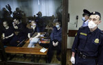 Members of the New Greatness group, who are charged with the organization of an extremist association, sit behind a glass in a courtroom prior to a court hearing in Moscow, Russia, Tuesday, July 14, 2020. Members of an opposition group dubbed New Greatness were arrested in 2018 on charges of creating an extremist group aiming to overthrow the government. The case was widely criticized as an example of politically motivated abuse anti-extremism laws. (AP Photo/Pavel Golovkin)