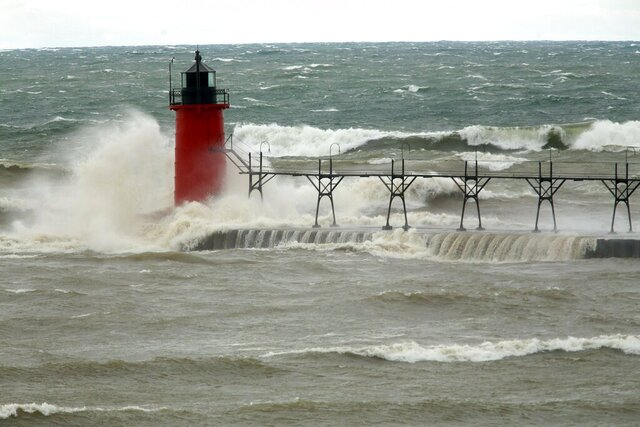 FILE - In this April 6, 2017 file photo, strong winds send huge waves at the Lake Michigan shoreline at South Haven Michigan. A decade-old program that has pumped $2.7 billion into healing long-term injuries to the Great Lakes environment has received authorization from Congress to continue another five years. The U.S. Senate voted unanimously Sunday, Dec. 20, 2020, to extend the Great Lakes Restoration Initiative, which the House did earlier this year. (Mark Bugnaski/Kalamazoo Gazette via AP, File)