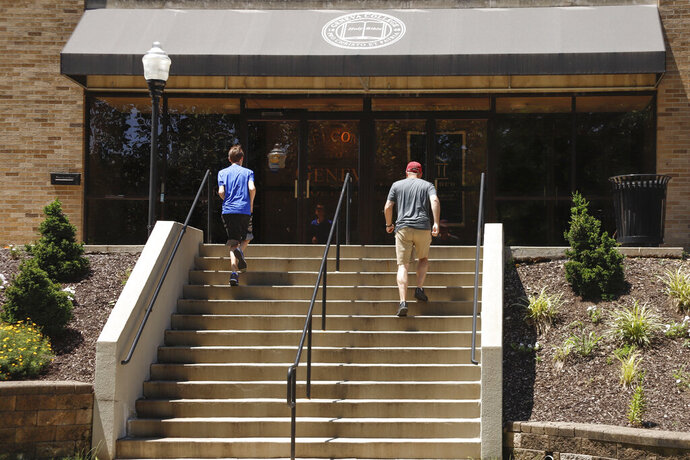 In this July 13, 2019, photo visitors walk the stairs to Alexander Hall on the campus of Geneva College in Beaver Falls, Pa. Whether it's money for books, living expenses or something else, students starting the new school year may quickly realize their financial aid won't cover all the costs of college. (AP Photo/Keith Srakocic)