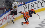 Edmonton Oilers' Kris Russell (4) is checked by Chicago Blackhawks' Kirby Dach (77) during the second period of an NHL Stanley Cup playoff hockey game in Edmonton, Alberta, Saturday, Aug. 1, 2020. (Jason Franson/The Canadian Press via AP)